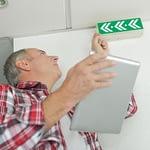 Mann med nettbrett kontrollere nødlys under årskontroll